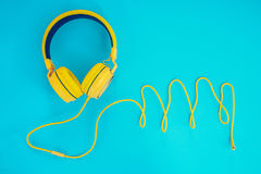 Yellow headphones or earphone computer on a blue pastel background.  Stock Photography