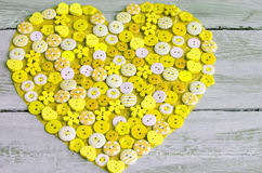 Yellow heart covered with colorful buttons. Stock Photography