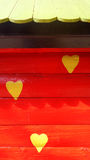 Yellow heart shapes on red wood wall Stock Image