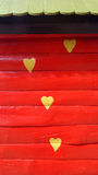 Yellow heart shapes on red wood wall Royalty Free Stock Photos