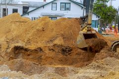 Yellow heavy duty digger working in excavation pit. On background of residential complex construction house industry sand earth soil industrial dirt land royalty free stock images