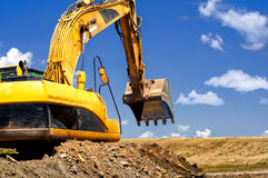 Yellow, heavy duty excavator moving soil and sand. On road construction site Stock Photo