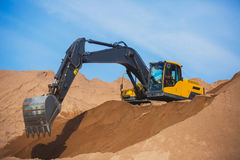 Yellow heavy excavator and bulldozer excavating sand and working during road works, unloading sand and road metal. During construction of the new road royalty free stock images