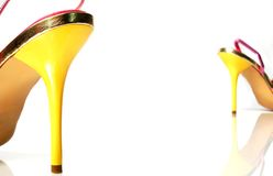 Yellow heels separated. Yellow high heels separated by white space. Heel on the back is out of focus. Heels reflecting on white surface stock images