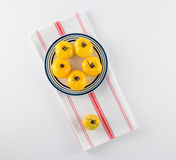 Yellow Heirloom Tomatoes on Stoneware Plate. Ripe yellow heirloom tomatoes on blue and green striped stoneware plate, on red and white French towel stock photography