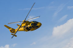Yellow Helicopter flight in cloudy sky Stock Photos