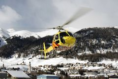A yellow helicopter flying up in the air over the small town in Engadin St moritz Switzerland in the alps for sightseeing in winte. R Stock Images