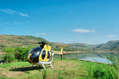 Yellow helicopter on lake island Royalty Free Stock Images
