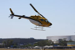 Yellow helicopter in a low fly over Royalty Free Stock Photography