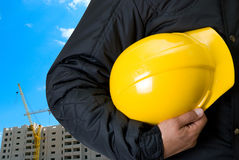 Yellow helmet. Closeup  of Yellow helmet at builder hands on building background Royalty Free Stock Images