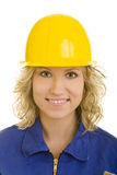 Yellow helmet. Blonde woman in a blue jumpsuit wearing a yellow hardhat royalty free stock photos