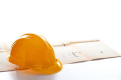 Yellow helmet on a blue print. With white background Stock Photography