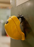 Yellow helmet. A yellow, hard plastic helmet hanging on a green metallic wall under a message board Stock Images