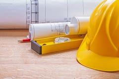 Yellow helmet level blueprints pencil on wooden Royalty Free Stock Photo