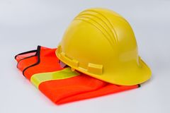 Yellow helmet and orange vest. The yellow helmet placed on orange vest with Reflective on yellow color on white background, safety work concept Stock Images