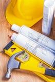 Yellow helmet rolled blueprints hammer level on Royalty Free Stock Photo