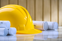 Yellow helmet and rolls of blueprints on table Stock Photos