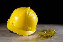 Yellow helmet, safety goggles and work gloves for the worker on Royalty Free Stock Images