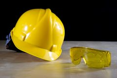 Yellow helmet, safety goggles and work gloves for the worker on Stock Image