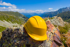Yellow helmet on a stone Stock Image