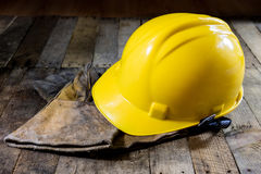 Yellow helmet and welding gloves. Old wooden table. Stock Photos