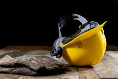 Yellow helmet and welding gloves. Old wooden table. Stock Images