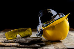 Yellow helmet and welding gloves. Old wooden table. royalty free stock photography