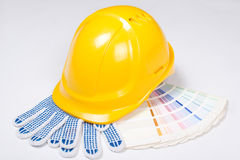 Yellow helmet, work gloves and colorful palette over white Stock Photo