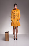 Yellow high. Beautiful brunette lady wearing a yellow coat ready to go Stock Image