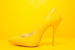 Yellow high heels shoes. Side view of high heels shoes on yellow background royalty free stock photos