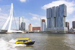 A yellow high-speed water taxi with in the background the Erasmus bridge and the Hotel nhow Rotterdam.  stock image