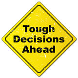"Tough decisions ahead. Yellow highway style sign board with text ""tough decisions ahead"" in black grunge lettering, white background Stock Images"