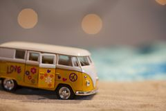 Yellow hippie van with peace sign on a sandy beach Royalty Free Stock Photography