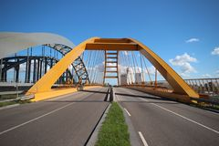 Yellow Hogeweidebrug suspension bridge in Utrecht with seperate lanes for traffic and for busses. With the coffee factory of Jacobs Douwe Egberts on background stock photo