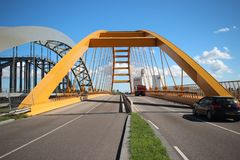 Yellow Hogeweidebrug suspension bridge in Utrecht with seperate lanes for traffic. And for busses with the coffee factory of Jacobs Douwe Egberts on background royalty free stock photos