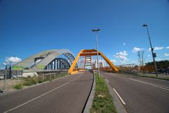 Yellow Hogeweidebrug suspension bridge in Utrecht with seperate lanes for traffic. And for busses with the coffee factory of Jacobs Douwe Egberts on background stock photography