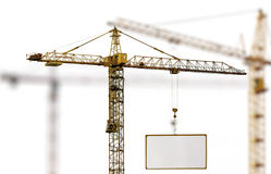 Yellow hoisting crane with advertisement hoardin Royalty Free Stock Images