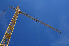Yellow hoisting crane on blue sky Stock Photography