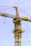 Yellow hoisting crane and blue sky Stock Image