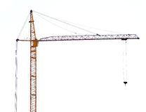 Yellow hoisting crane with dark boom Royalty Free Stock Photography