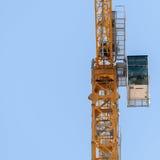 Yellow hoisting crane  on sky background Stock Photography