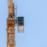 Yellow hoisting crane  on sky background Royalty Free Stock Photos