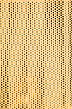 Yellow hole pattern vertical. Radiator grill from vintage farm tractor closeup, uniform small holes, vague shapes behind Stock Image