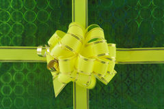 Yellow holiday bow over  green background Royalty Free Stock Images
