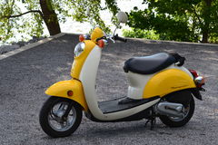 Yellow Honda metropolitan scooter parked on gravel Stock Photography