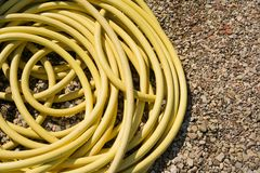 Yellow Hose Pipe. Coiled yellow hose pipe on a gravel background - copy space provided stock photo