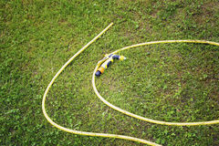 Yellow hose for watering Stock Photo