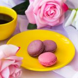 Yellow hot drink cup and macaroons royalty free stock photography