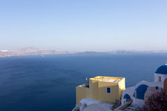 Yellow house and blue roof on a background of sea and mountains. Santorini Royalty Free Stock Images