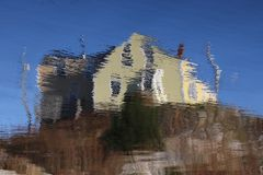 Yellow House Distorted Reflection. A reflection of a yellow house on rippling water Stock Photo
